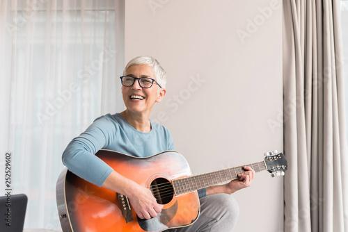 Smiling woman playing guitar - 252529602