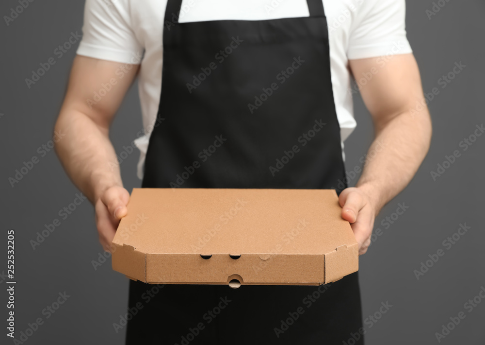 Fototapeta Waiter in apron with pizza box on grey background, closeup. Food delivery service
