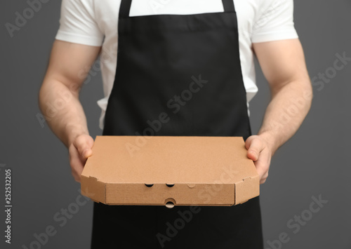 Fotomural Waiter in apron with pizza box on grey background, closeup