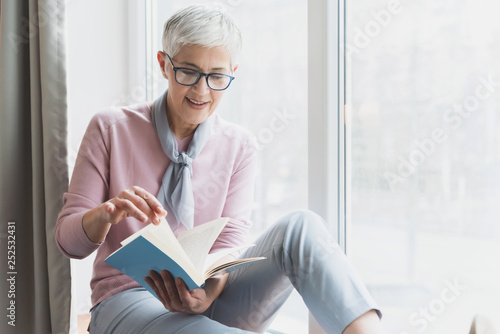 Fotografie, Obraz  Mature woman reading book