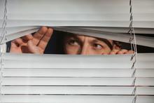 Curious Man Looking Through Venetian Window Blinds