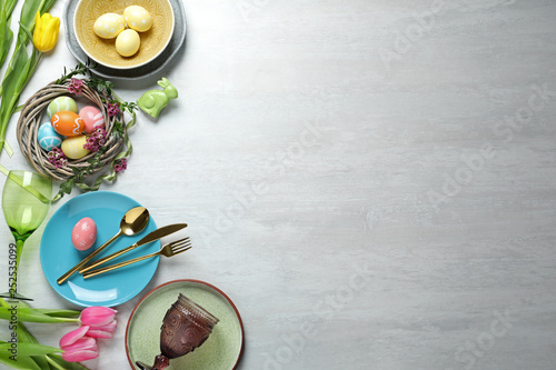 Fotografía Festive Easter table setting with painted eggs on wooden background, top view