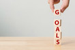 Hand putting wood cube with word GOALS. Concept of your business target or lifestyle