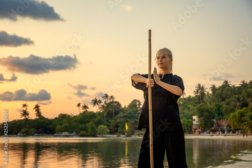 Valokuvatapetti Young beautiful girl woman blond doing kung fu with bamboo stick on the seashore