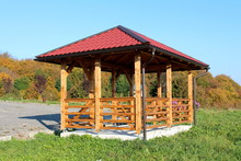 Wooden Gazebo Structure With New Roof And Gutter Mounted On Concrete Foundation Next To Uncut Grass And Gravel Parking With Dense Trees And Clear Blue Sky Background