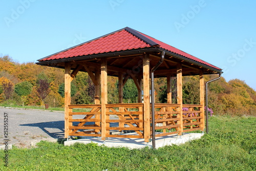 Fototapeta Wooden gazebo structure with new roof and gutter mounted on concrete foundation