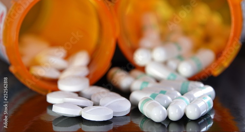 Photo Two types of prescription drugs spilling from containers