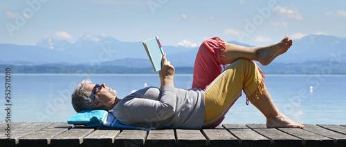 Leinwand Poster  Seniorin im Frühling am See beim Lesen