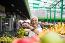 Senior Woman Buying Fruits On Market