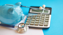 Piggy Bank With Stethoscope Isolated On Blue Background. Concept Of Financial Literacy. Creating And Maintaining A Budget. Keeping Their Finances On Track. Ruin Loan History