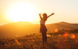 canvas print picture - Happy woman jumping and enjoying life  at sunset in mountains.