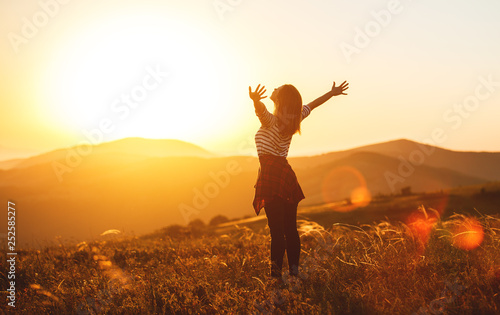 Obraz Happy woman jumping and enjoying life  at sunset in mountains. - fototapety do salonu