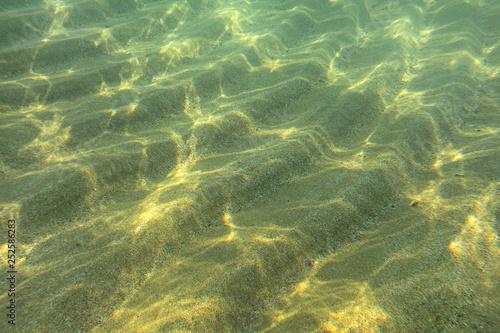 Fototapeta Underwater photo - sun shines on sand