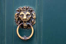 Golden Door Knocker In The Shape Of Lion With Ring On A Wooden Door