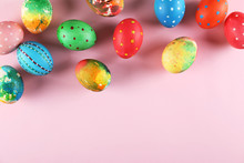 Bunch Of Colorful Tie Dye And Polka Dot Painted Easter Eggs On Pale Pink Paper Background With A Lot Of Copy Space For Text. Top View, Flat Lay, Close Up. Easter Greeting Card Concept.