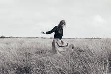 Woman Walking Alone In Meadow