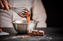 Chef Whisking Melted Chocolate In A Mixing Bowl
