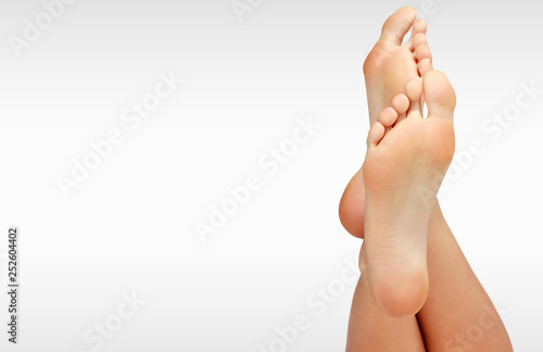Foto op Canvas Pedicure Beautiful woman's bare feet against a grey background with copyspace