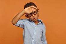 Human Facial Expressions And Body Language. Handsome African American Male Child In Round Eyeglasses Having Relieved Look, Breathing Air Out, Making Phew Sound, Whiping Sweat From His Forehead