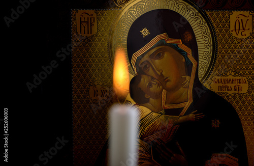 Orthodox icon of the Mother of God and baby Jesus and a blurred burning candle i Fototapeta