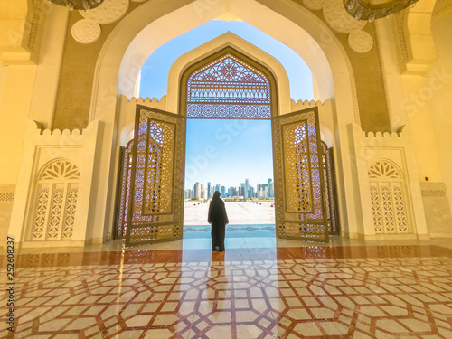 Fényképezés  Woman with abaya dress looks at views of skyscrapers of Doha West Bay skyline outdoors State Grand Mosque in Doha, Qatar, Middle East, Arabian Peninsula