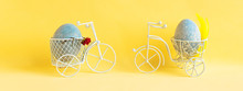 Two Easter Eggs Ride Towards Each Other On Bicycles On A Yellow Background.