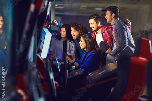 Foto A group of friends playing arcade machine.