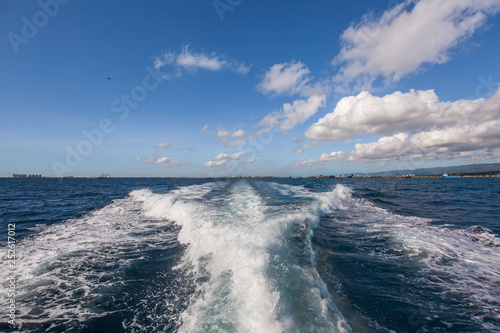 Fotografie, Obraz  Wake water of a fast ferry speedboat with white foam, blue sky and deep blue sea