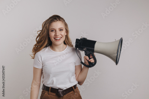 Fotografía  Pretty curly hair model in a white t-shurt holding megaphonecand smiling