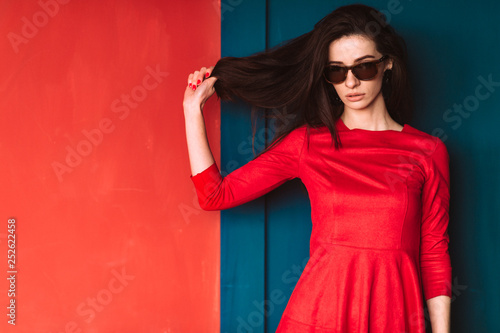 Obraz na plátne  Beautiful fashion girl with long hair, spanish appearance in sunglasses and red elegant dress posing on blue red wall in studio