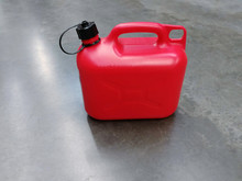 Red Plastic Gas For Flammable Liquids With A Black Lid On The Concrete Floor