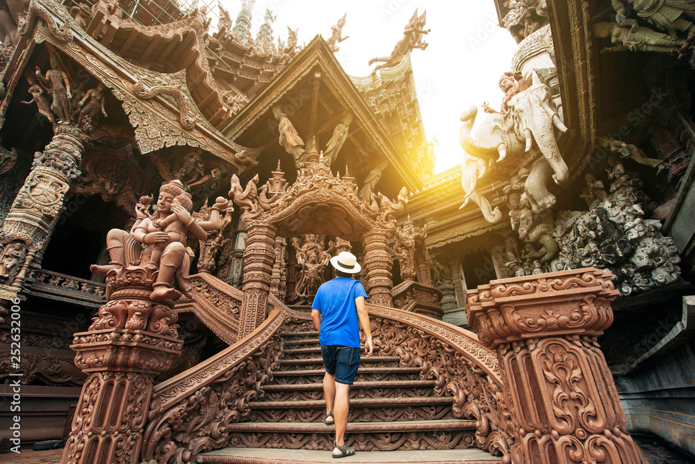 Fototapety, obrazy: A man tourist is sightseeing inside the Ancient wooden Sanctuary of Truth in Pattaya, Thailand.
