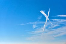 White Clouds As An X Shape Sign Against A Saturated Blue Sky With Copy Space On The Left