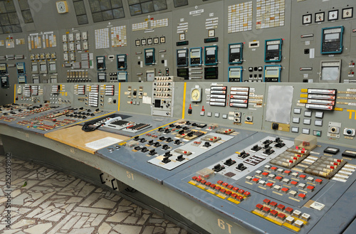 Fotografie, Obraz  Operator sits in front of the  main control board in a control operations room o