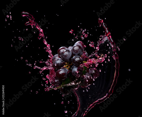 Bunch of grapes with red juice splash isolated on black background Fototapete