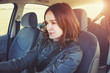 portrait of pretty young smiling woman driving a car, sunny day
