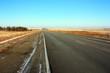 An empty asphalt road in a field