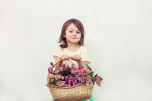 Little Child Girl Beautiful, Cute And Happy With Flowers On White Wall Background