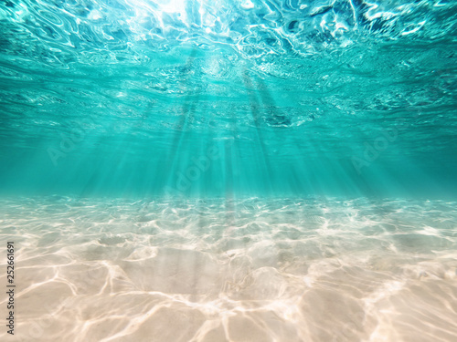 Obraz underwater background  deep blue sea and beautiful light rays with sandy floor - fototapety do salonu