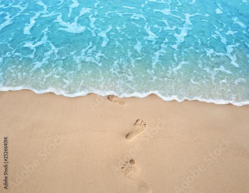 Soft blue ocean wave on clean sandy beach with foot print Fototapete