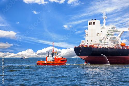 Fotomural Tanker ship with escorting tug leaving port.