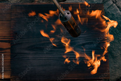 La pose en embrasure Feu, Flamme fire flame on black board wood texture, and gas torch