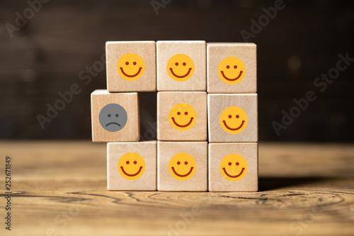 Fotografie, Obraz  Viele Würfel mit lächelnden Smileys und einer der unzufrieden ist