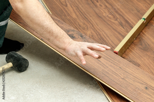 Foto op Canvas Trappen master in blue gloves makes laying. floorboard. there is a level. and rubber hammer.