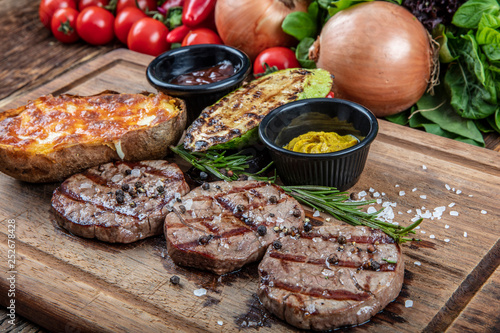 Foto op Canvas Vlees grilled lamb steak served with zucchini, potatoes, mustard and sauces on wood.