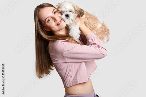 Fotografia, Obraz  Positive European woman with long hair embraces her favourite pet with fluffy fu