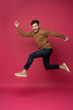 Happy excited cheerful young man jumping and celebrating success isolated on a pink background.