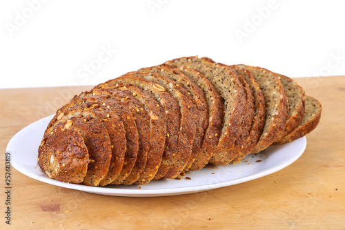 Fotografie, Obraz  Sliced Loaf of Homemade Pumpkin Seed Bread on White BG with copy space