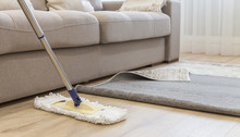 Cleaning Floor With Mop Under Carpet In Living Room