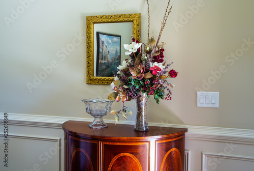 Fotografie, Obraz  An old wood credenza in a foyer under a mirror with a crystal punch bowl and a f
